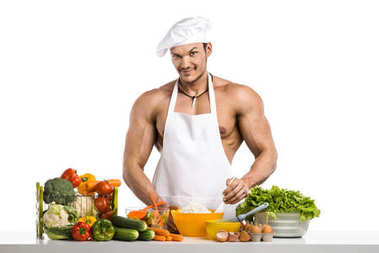 Man bodybuilder in white toque blanche and cook protective apron