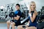 dívka a kluk cvičení s činkami v posilovně, fitness koncept