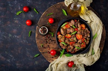 Chicken liver with tomatoes in frying pan