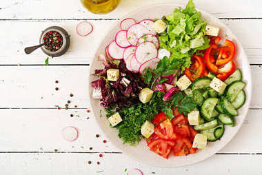 Mix salad from fresh vegetables and greens herbs in white bowl on wooden table