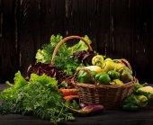 Zöldségek és zöld fűszernövények széles választékát. Piac. Zöldségek egy kosárban, a sötét háttér