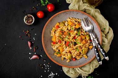 Vegan Fusilli vegetable paste with pumpkin, Brussels sprouts, paprika and carrot on a dark background. View from above