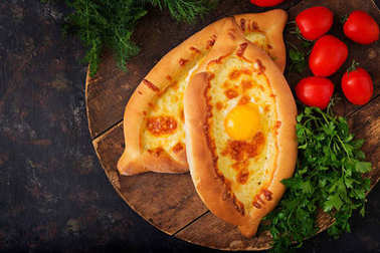 Khachapuri in Adjarian. Open pies with mozzarella and egsg. Georgian cuisine.