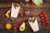 Mexické tacos s hovězím masem v rajčatové omáčce a avokádem salsa. Byt leží. Pohled shora
