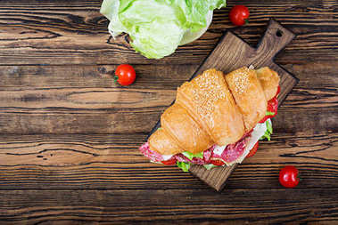 Tasty breakfast. Appetizing croissant with salami and, cheese and tomatoes. Flat lay. Top view