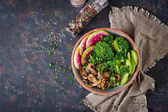 Vegán étel buddha tál asztalnál. Egészséges étel. Egészséges vegán ebéd tálba. Roston sült gomba, brokkoli, retek saláta. Lapos feküdt. Szemközti nézet.
