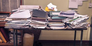 workplace with stack of old papers