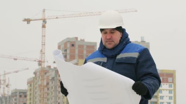 Polier mit Papierzeichnungsplan bei Bauprojekt