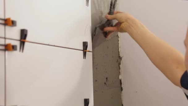 Worker putting tile glue on wall
