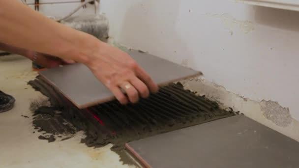 Pracovník pokládající dlaždice na podlahu