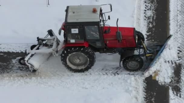 Traktor odstraňuje sníh z chodníků