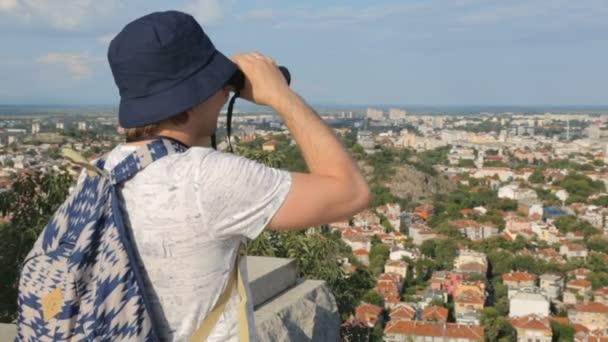 Mladý muž turista dívá dalekohledem nad městem