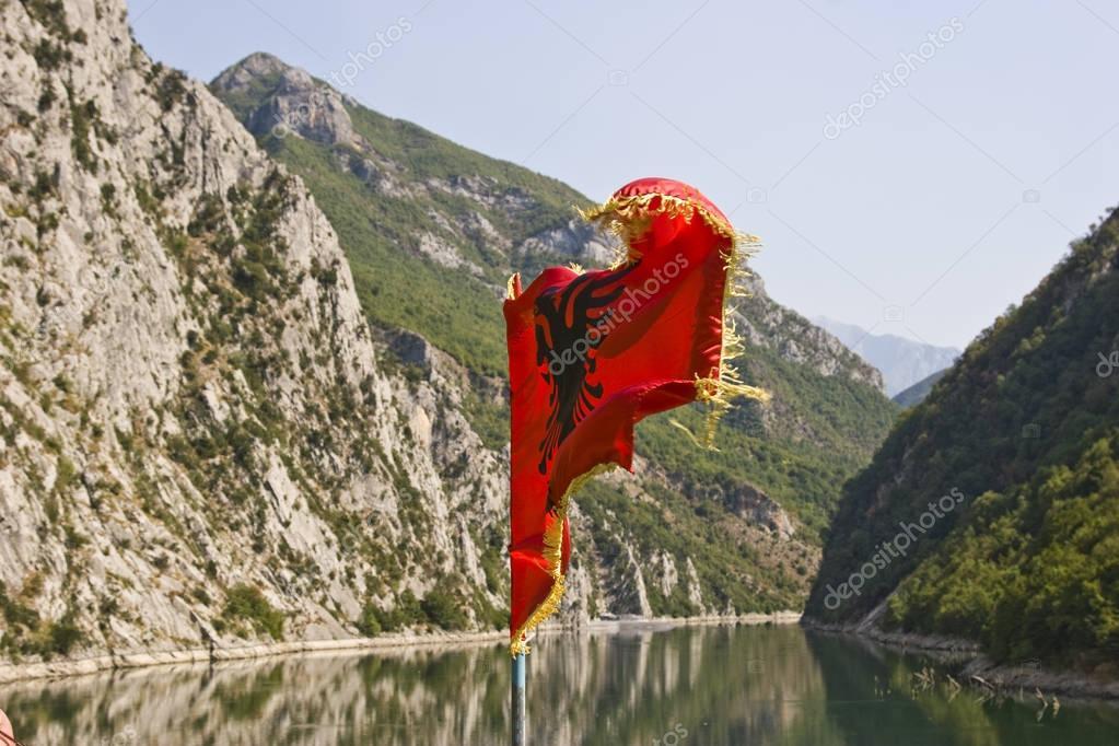 Albanian national flag on Komani lake