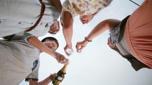Man gießt Champagner an Freunde