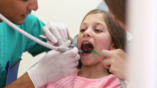 dentist fixing teeth of girl