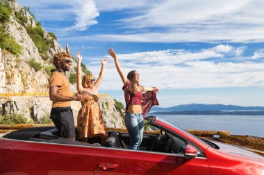 people waving from the convertible