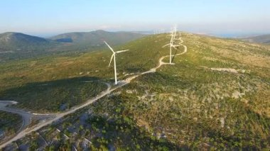 wind turbines on green sunlit hills