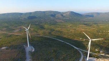 wind turbines on green sunlit hills
