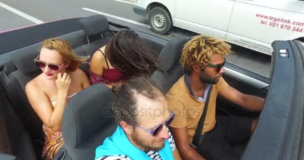 people having fun riding in convertible