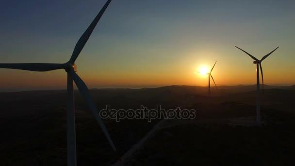 windmill blades rotating at sunset