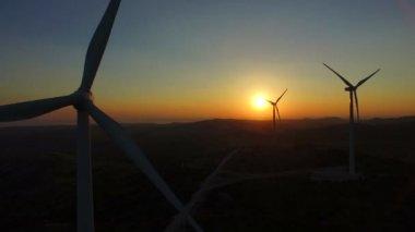 rotating windmill blades at sunset