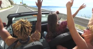 friends driving in convertible