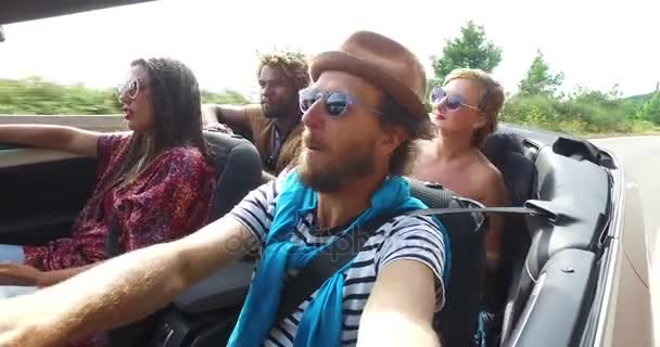 man driving friends in cabriolet
