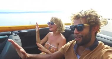 couple having fun riding in convertible