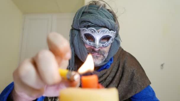 Mann beim venezianischen Karneval zündet eine Kerze an