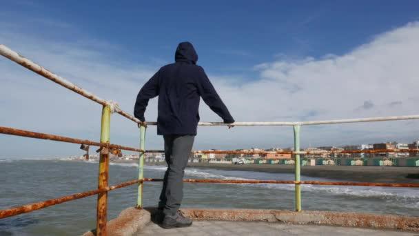 Zralý muž a moře za slunečného větrného dne