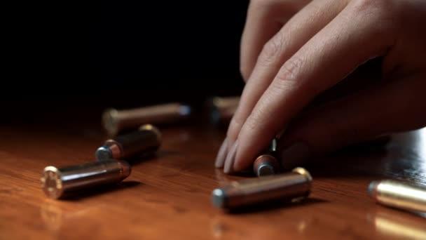 eine weibliche Hand nimmt eine Kugel 9 mm