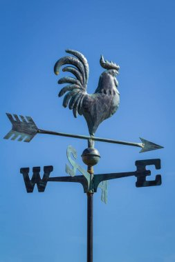 Weather vane showing direction of wind against clear blue sky, vertical