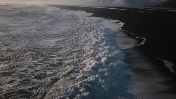 Letecký pohled na oceán s velkými vlnami, odhalující pláže s černým pískem a hory