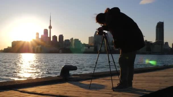 Fotograf mit Stativ und DSLR-Kamera fotografiert toronto Stadtlandschaft bei Sonnenuntergang