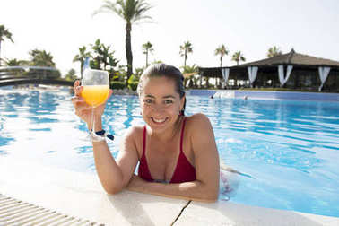 Woman by the pool with drink in a glass