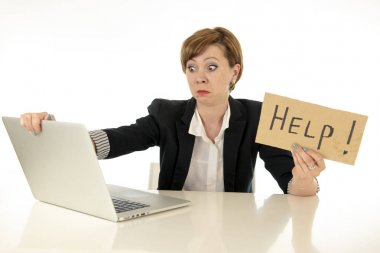 beautiful young red haired caucasian tired and frustrated business woman working on her computer holding a help sign at work office desk on a white background.Stress and business frustration concept