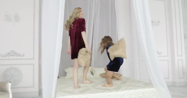 mladé dívky hrát s polštáři na lůžku v ložnici