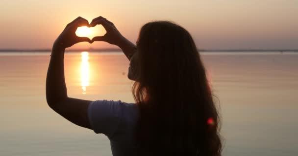 Silueta dívky, která dělá srdce s rukama při západu slunce.