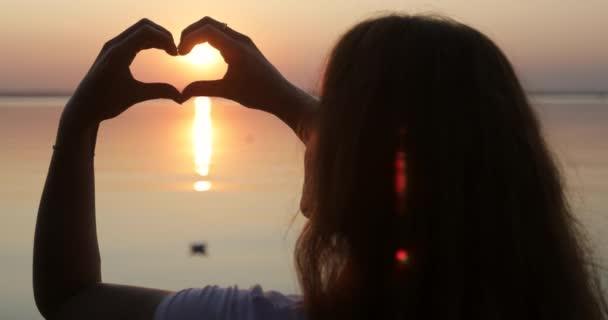 Rudé slunce v rukou mladé ženy.