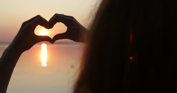 Zavřete hlavu a ruce. Silueta dívky, která dělá srdce s rukama při západu slunce.