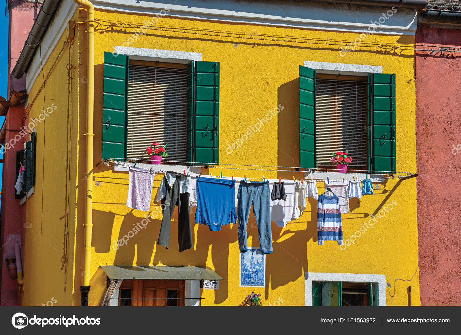 Close-up of windows on colorful walls and clothes hanging – Stock ...
