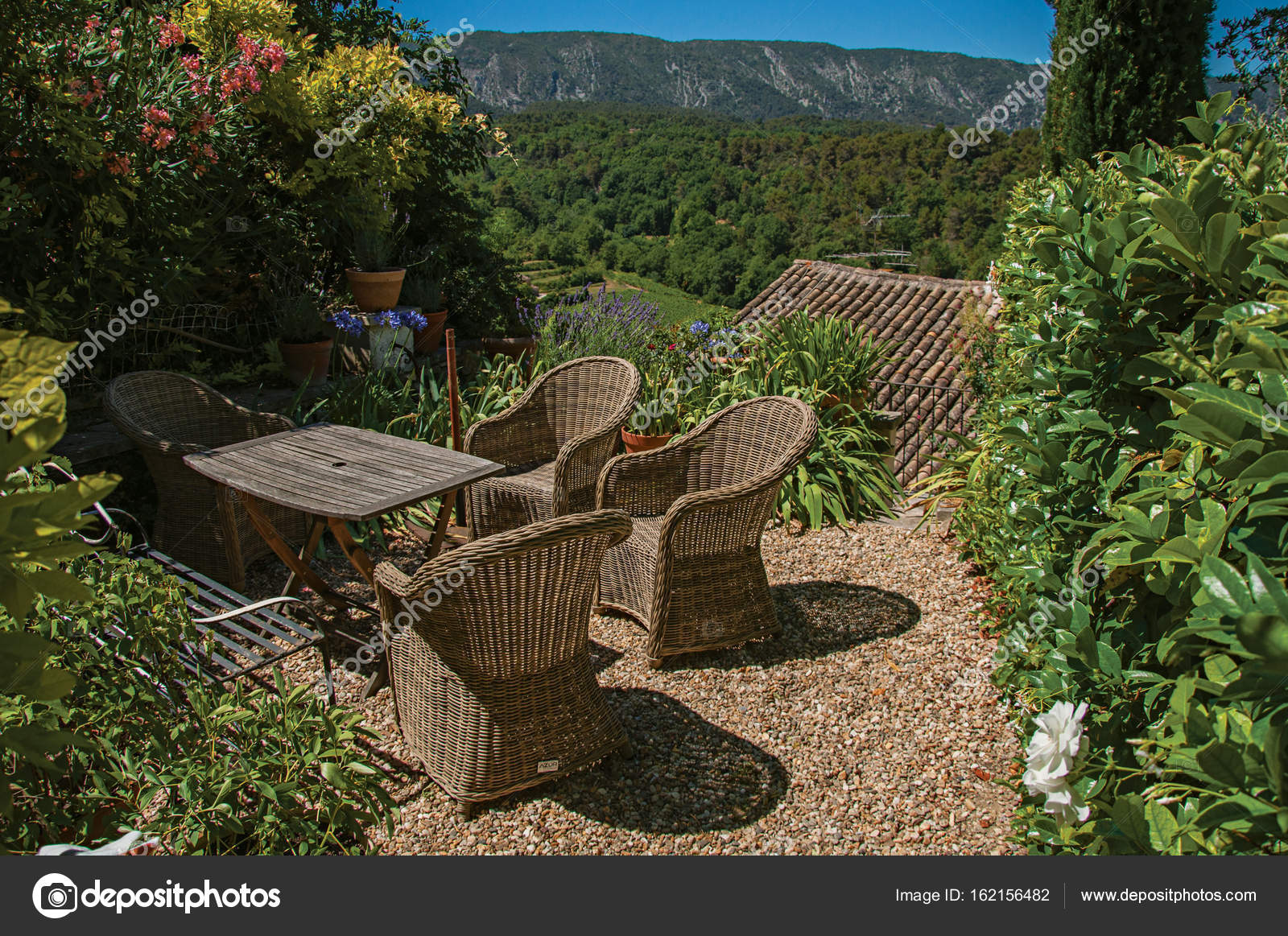 View of small garden with mountains and sunny blue sky in the ...