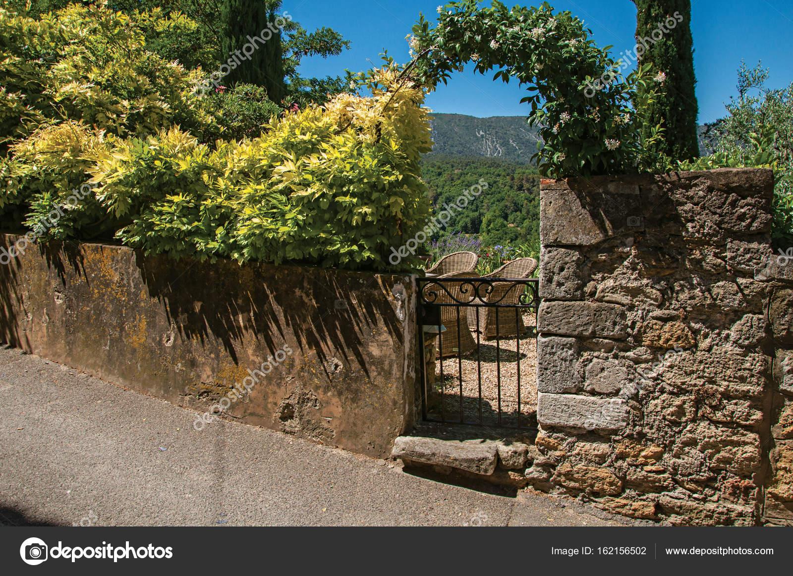 Stenen Muur Tuin : Uitzicht op kleine tuin achter ijzeren poort en stenen muur in het
