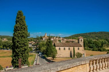 Panoramic view of the village of Lourmarin, its main street and hills in the background.