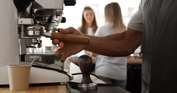 Foglalt café. Zár-megjelöl-ból afrikai barista így espresso lövés, kávé döngölőgép és tej futást. Lassú mozgás.