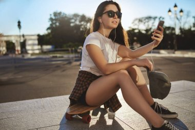 stylish and sassy teenage girl search perfect angle, taking selfie during skateboarding, wear sunglasses take-off snapback, listen music with wired earphones, sit on penny board at empty skate-park