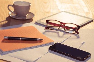 Eyeglasses and digital tablet on table