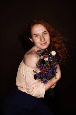 redhead girl holding cornflowers