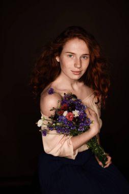 redhead girl holding wild flowers