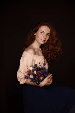 redhead girl holding wild flowers